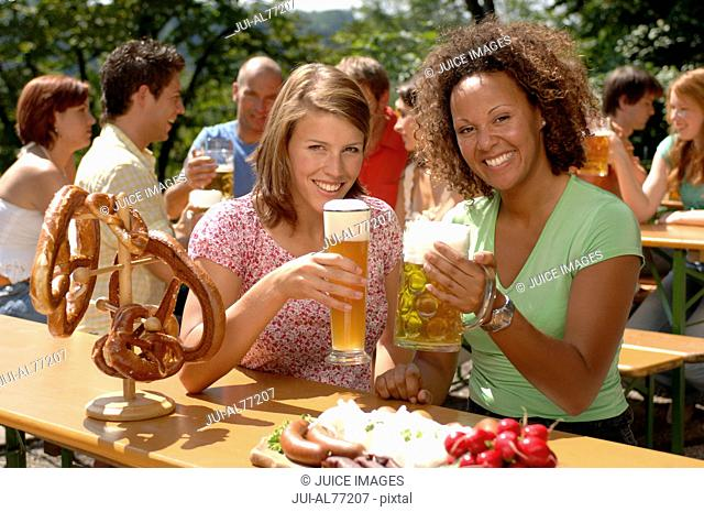 View of two young women raising their drinks, beergarden, Munich, Bavaria, Germany