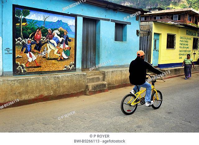 boy on a bike passing an eye-catching wall painting at a house fassade, Guatemala, Atitlan Lake, Santa Cruz la Laguna