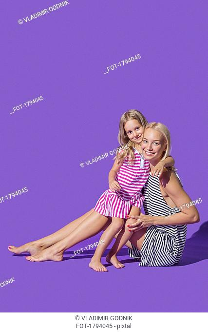 Portrait smiling mother and daughter hugging in striped dresses against purple background