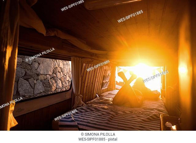 Spain, Tenerife, young woman lying in van, evening light