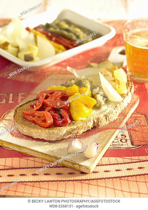 escalivada de pimientos rojos y amarillos, berenjena y patata, sobre tostada de pan de payes