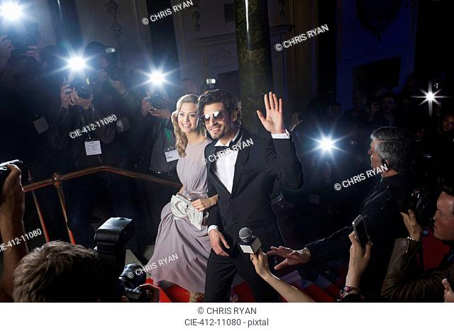 Well dressed celebrity couple waving to paparazzi on red carpet
