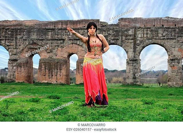 belly dancer with ancient Roman aqueducts ruins in the background
