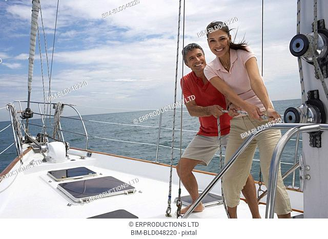 Multi-ethnic couple pulling rope on sailboat