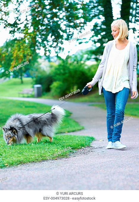 A pretty young blonde woman walking her dog