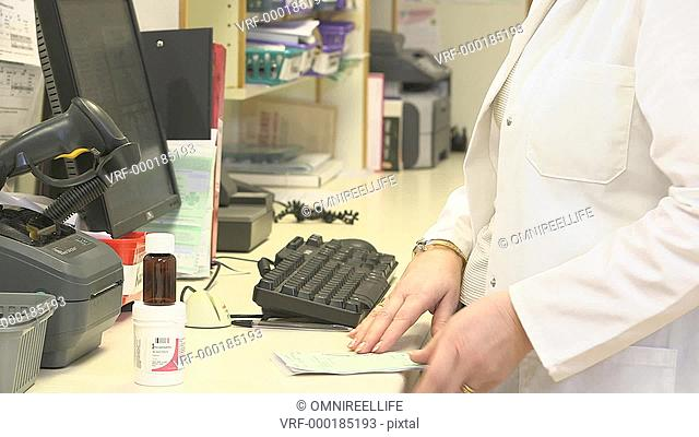 Female pharmacists printing out medicine labels