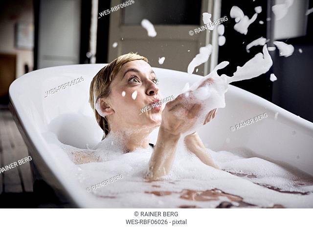 Blond woman taking bubble bath blowing foam in the air