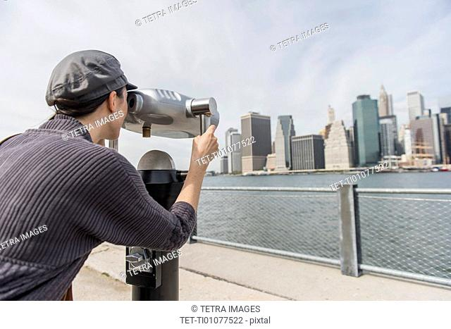 Woman watching cityscape through coin-operated binoculars
