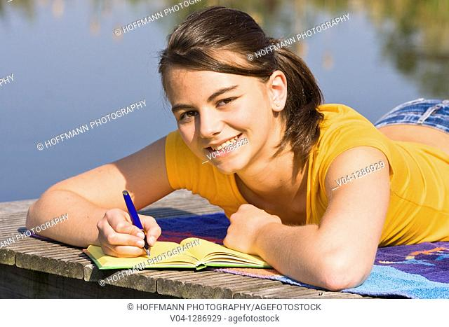 A young girl writing into her diary at a lake, smiling at the camera
