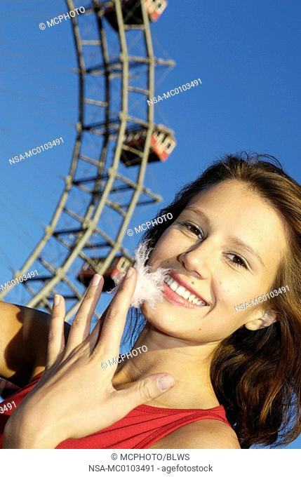 amusement park Prater Vienna, young woman with candy floss, Giant Ferry Wheel