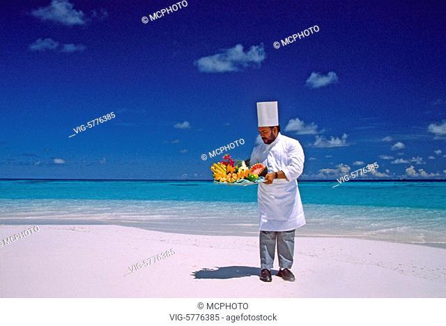 Ein Koch am Strand mit exotischen Fruechten, Malediven - Bandos, Malediven, 15/04/2009