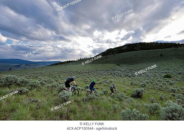 A group of mountain bikers enjoy the ride at sunset in the Lac Du Bois Protected Grasslands over Kamloops, Thompson Okanagan region, British Columbia, Canada