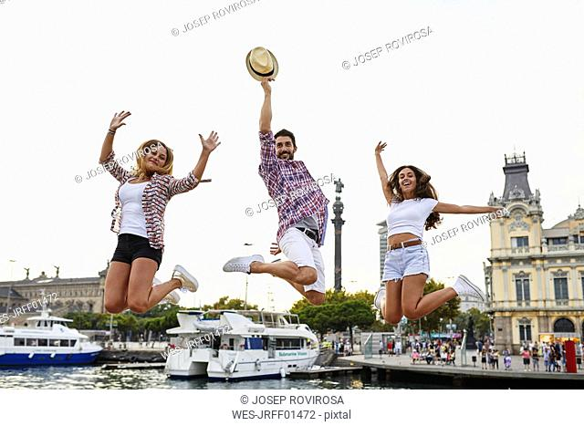 Spain, Barcelona, three friends jumping in the city center near the sea