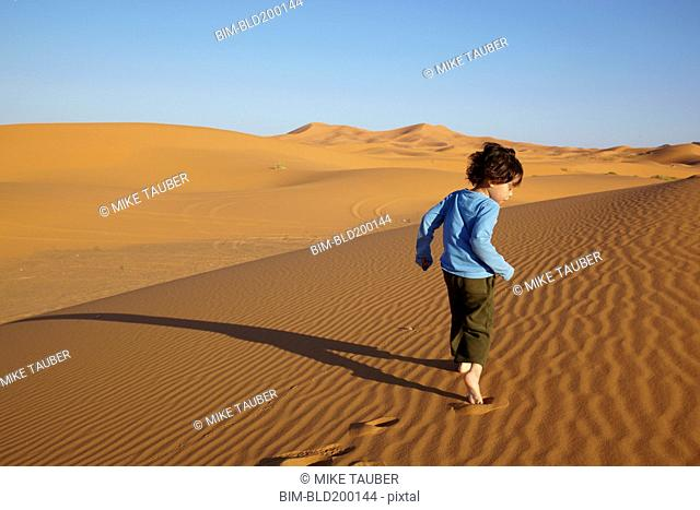 Mixed race boy running in desert