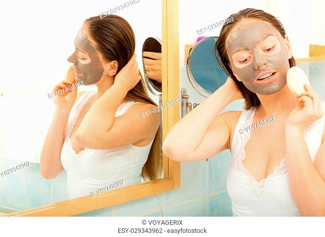 Beauty procedures spa and skin care concept. Young woman with facial clay mask in bathroom holds sponge to remove mud