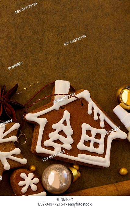 christmas gingerbread frosted home cookies with christmas decorations on cooking paper with copy space