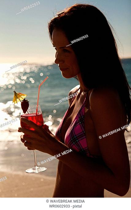 Woman with a cocktail while wearing a bikini