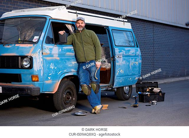 Portrait of man standing next to camper van