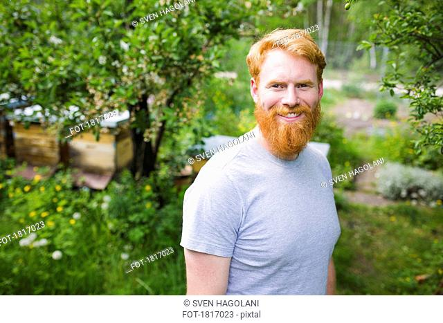 Portrait smiling, confident man with red hair in garden