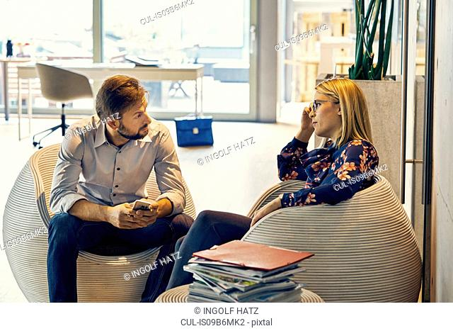 Businesswoman talking to male colleague in lounge area