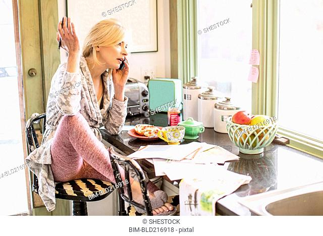 Caucasian woman paying bills on telephone in kitchen
