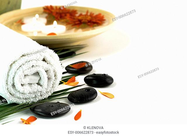 Spa setting with white towel, pebbles, candles and flowers, on white with copy space