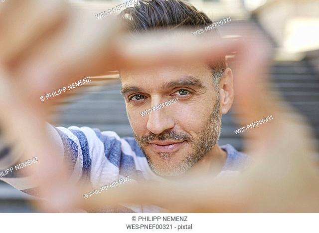 Portrait of mature man building frame with his fingers