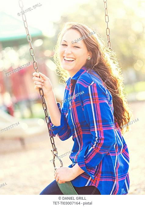 Woman swinging in playground