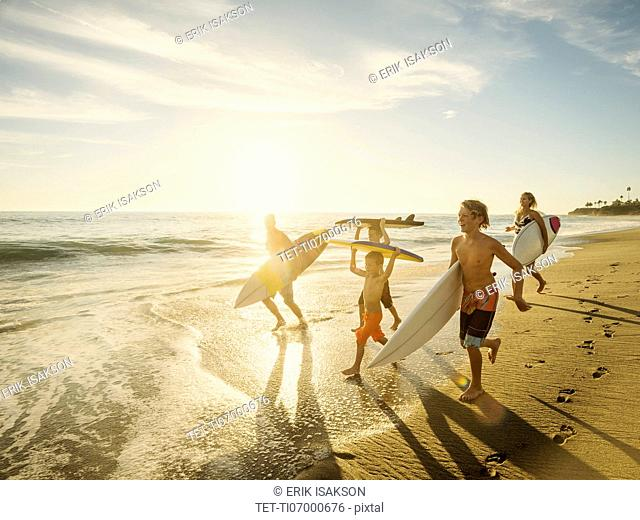 Family with three children (6-7, 10-11, 14-15) with surfboards on beach