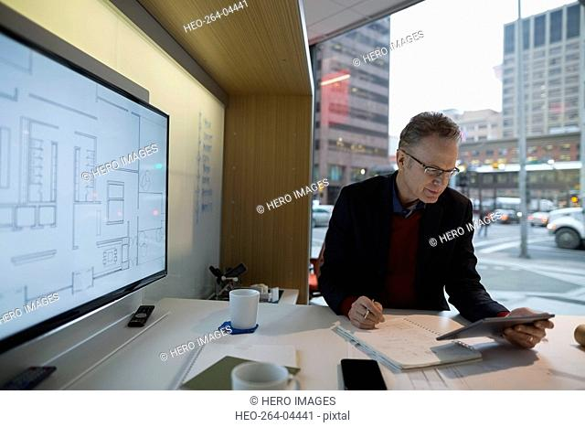 Architect with digital tablet drafting blueprints urban office