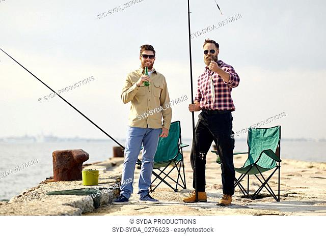 happy friends with fishing rods and beer on pier