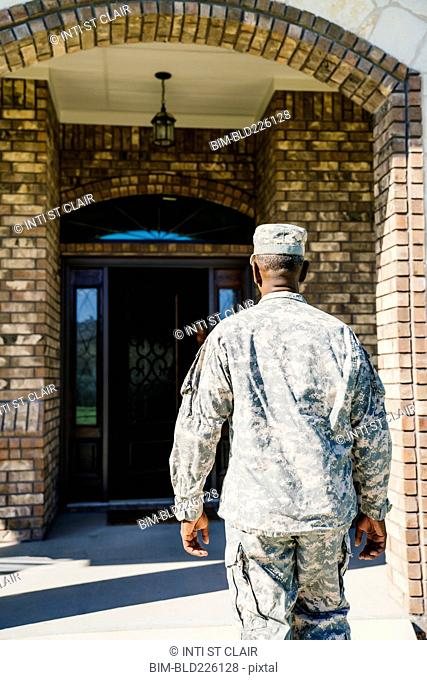 Black soldier approaching doorway