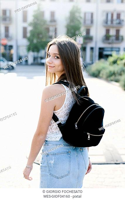 Portrait of smiling young woman with backpack in the city