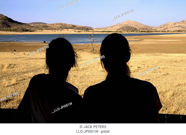 Silhouette of two young girls in a safari hide lookout, Pilanesberg National Park, North West Province, South Africa