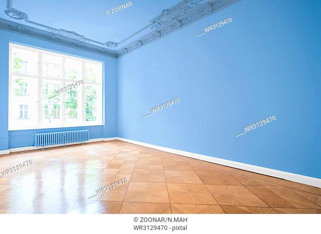 empty room in new apartment - blue walls and wooden floor