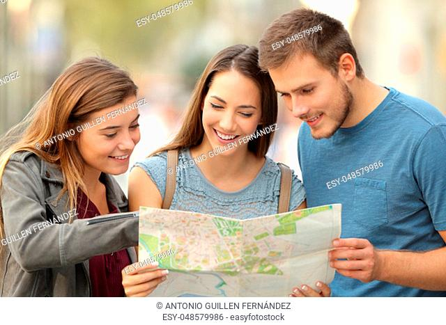 Three happy tourists consulting a paper map to find a location on the street
