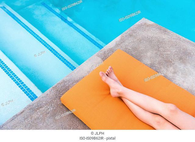 Overhead view of boy's legs lying on poolside