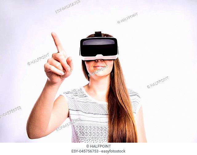 Beautiful woman in white t-shirt wearing virtual reality goggles reaching up. Studio shot on gray background