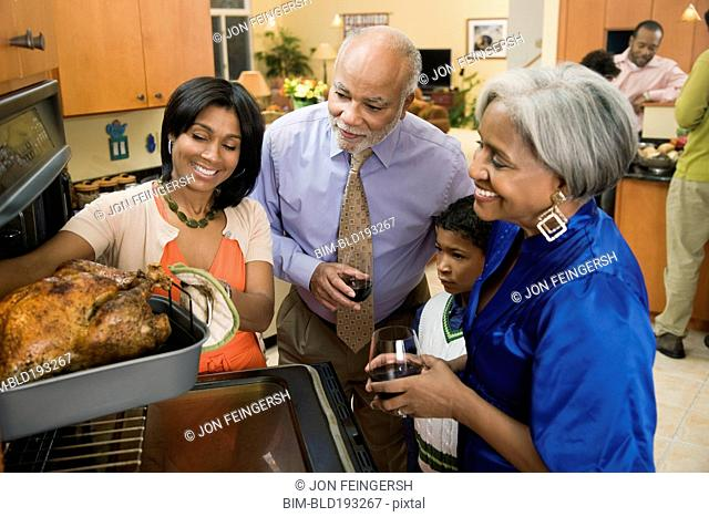 African American family watching woman take Thanksgiving turkey from oven