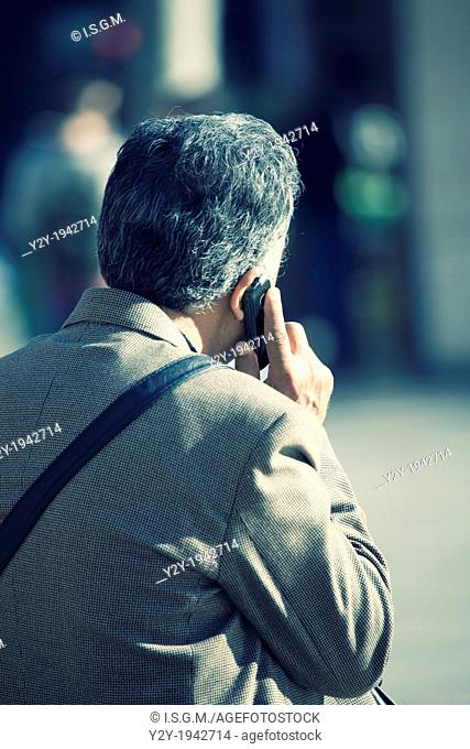 Man talking on phone with white hair, and Prince of Wales jacket. Valencia City, Spain