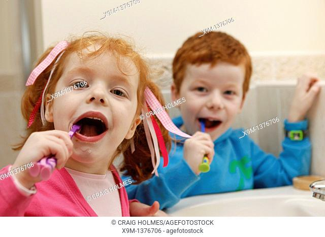 Little boy and girl at home, brushing teeth in bathroom