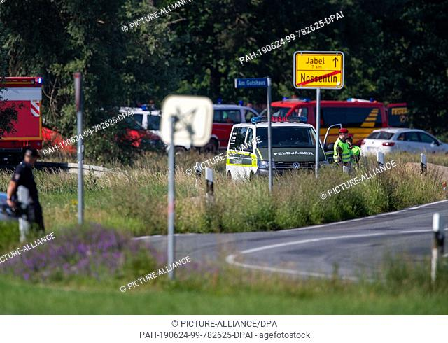 24 June 2019, Mecklenburg-Western Pomerania, Jabel: Fire brigades and Bundeswehr units are located near the crash site of a Eurofighter
