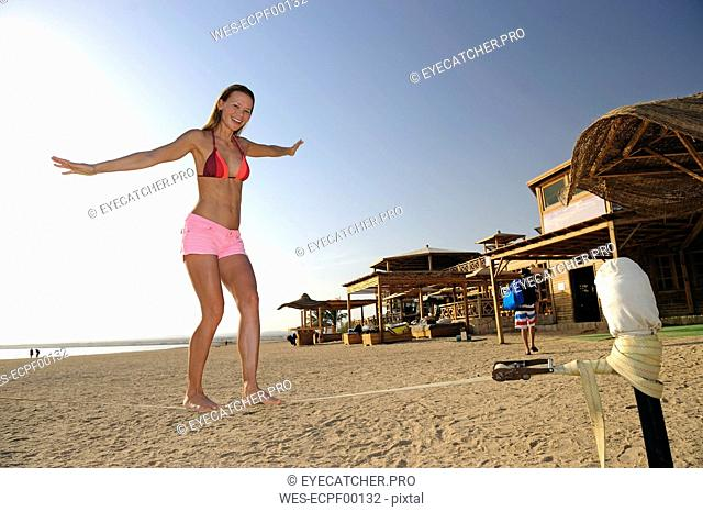 Egypt, Soma Bay, happy woman on the beach balancing on a slackline