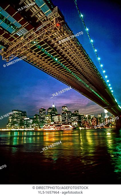 New York, NY , USA - Looking up, Cityscape, Buildings on East iver with Brooklyn Bridge, Skyline at Night