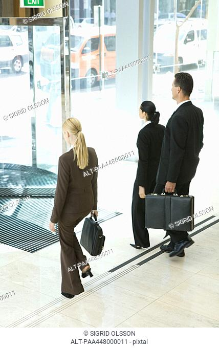 Business associates with briefcases exiting office lobby