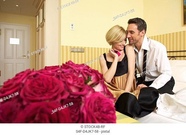 Couple on bed, bunch of roses in foreground