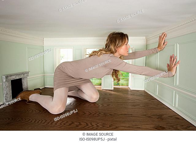 Giant young woman trapped in small room