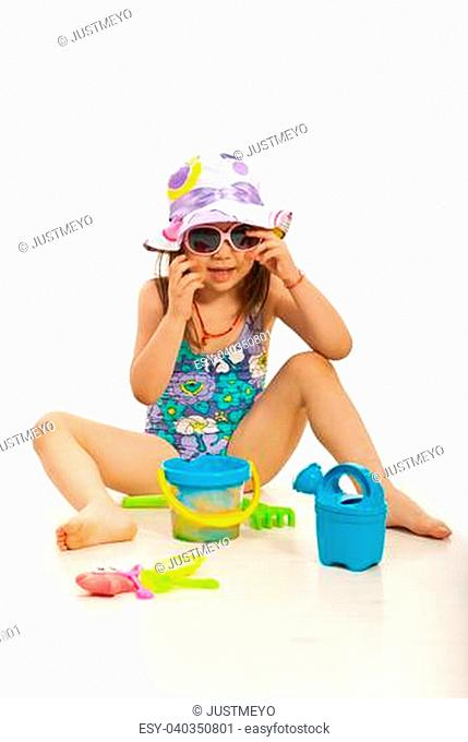 Funny girl with hat and sunglasses playign with beach toys