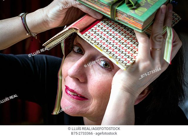 Middle-aged woman with a book over her head looking at camera