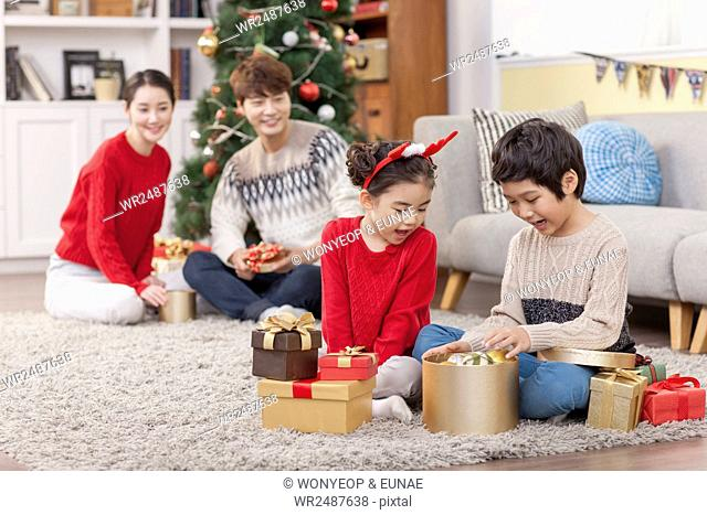 Boy and girl delighted with Christmas present boxes and their parents watching them with smiles